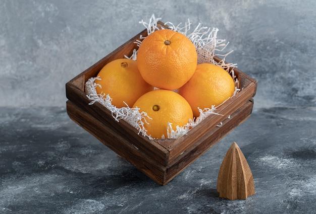 Świeże dojrzałe pomarańcze w drewnianym pudełku.
