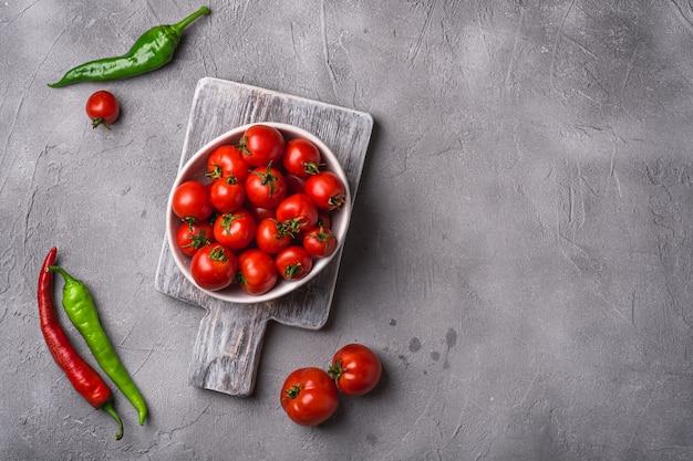 Świeże, dojrzałe pomidory w misce na starej drewnianej desce do krojenia z ostrą papryką chili