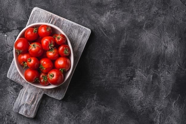 Świeże, dojrzałe pomidory w misce na starej drewnianej desce do krojenia