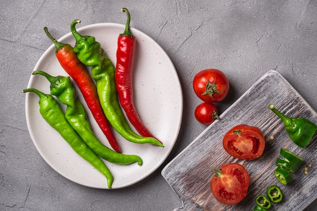 Świeże, dojrzałe pomidory w pobliżu starej drewnianej deski do krojenia z ostrą papryką chili w płycie, beton z kamienia