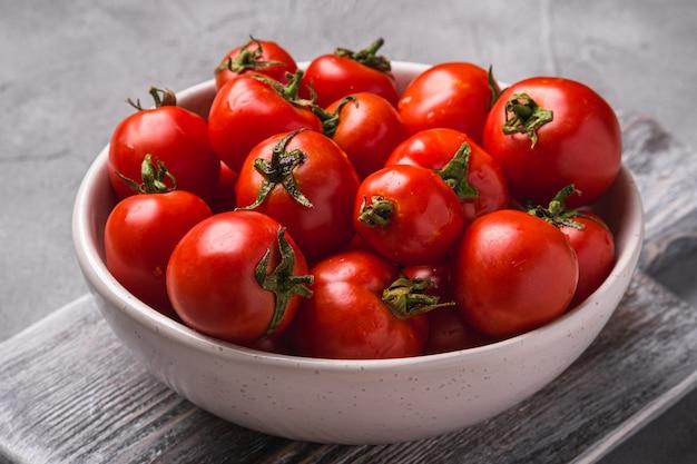 Świeże, dojrzałe pomidory z kropli wody w misce na starej drewnianej desce do krojenia