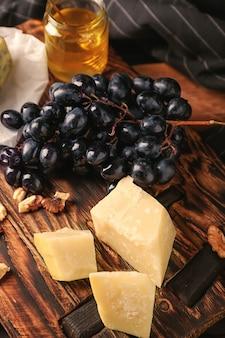 Świeże dojrzałe soczyste winogrona z parmezanem na drewnianej desce