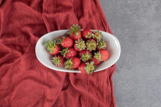 Świeże dojrzałe truskawki w białym pucharze. zdjęcie wysokiej jakości