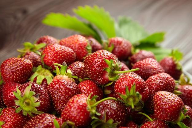 Świeże, dojrzałe truskawki z zielonymi liśćmi na niewyraźne drewniane tło, zbliżenie. czerwone letnie jagody