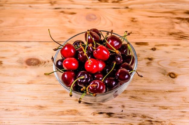Świeże dojrzałe wiśnie w szklanej misce na rustykalnym drewnianym stole