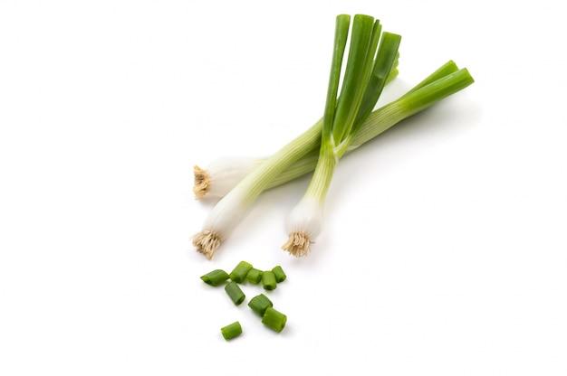 Świeże, dojrzałe zielone dymki (szalotki lub szalotki) ze świeżą posiekaną zieloną cebulą na białym tle