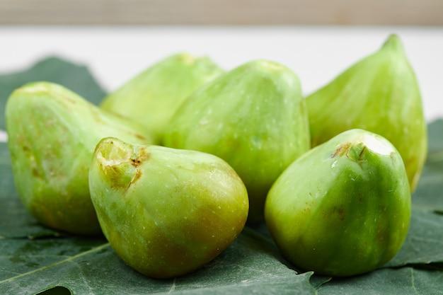 Świeże, dojrzałe zielone figi na liściach. wysokiej jakości zdjęcie
