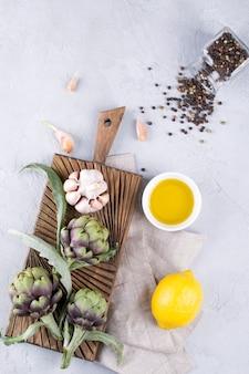 Świeże, dojrzałe zielone karczochy na desce do krojenia gotowe do gotowania i składniki czosnek, cytryna i oliwa z oliwek