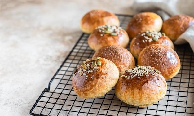 Świeże domowe bułeczki dyniowe z brązowym cukrem lub nasionami, jasne tło betonowe. jesienna piekarnia.