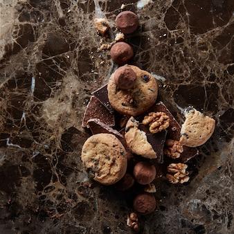 Świeże domowe ciasteczka czekoladowe z czekoladowymi cukierkami na ciemnej marmurowej powierzchni.