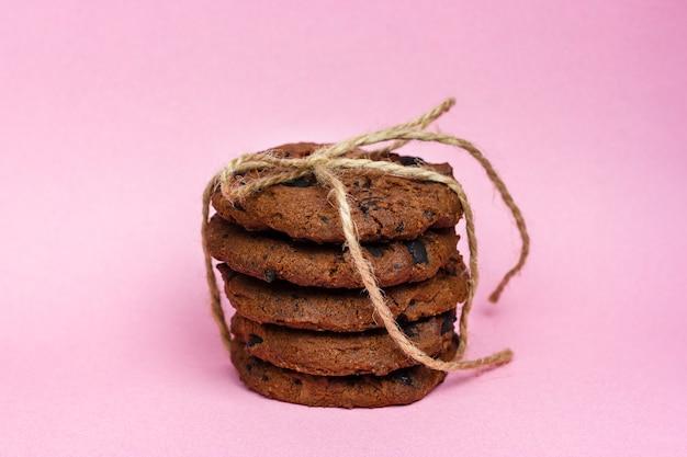 Świeże domowe ciasteczka czekoladowe związane sznurkiem na różowym tle.