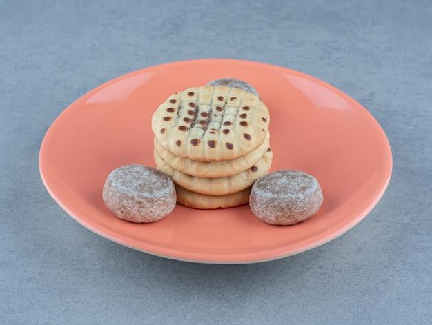 Świeże domowe ciasteczka na pomarańczowym talerzu.