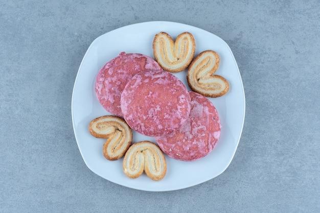 Świeże domowe ciasteczka. różowe ciasteczka na białym talerzu.