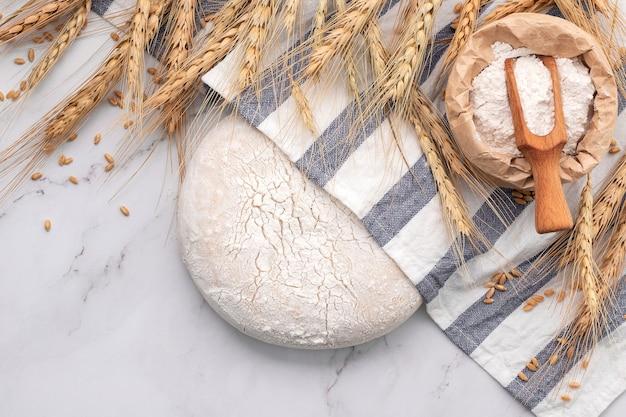 Świeże domowe ciasto drożdżowe na marmurowym stole z kłosami pszenicy i wałkiem do ciasta.