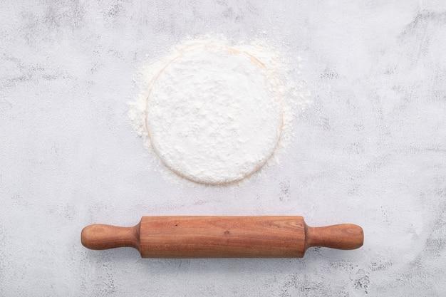 Świeże domowe ciasto drożdżowe spoczywające na białym tle concreate płasko leżące z wałkiem