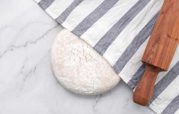 Świeże domowe ciasto drożdżowe spoczywające na marmurowym stole z płaskim ułożeniem wałka do ciasta.