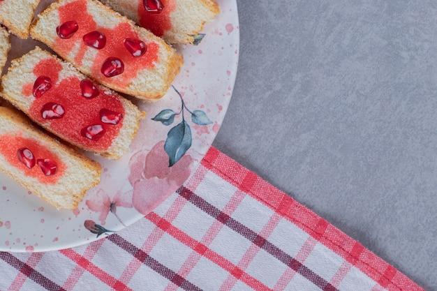 Świeże domowe ciasto z nasionami granatu na białym talerzu