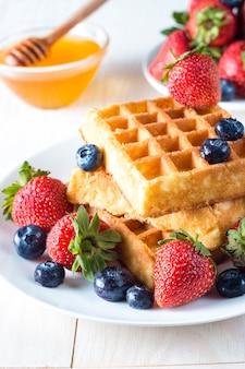 Świeże domowe jedzenie jagodowych gofrów belgijskich z miodem, czekoladą, truskawką, jagodą, syropem klonowym i śmietaną. zdrowy deser śniadanie koncepcja z sokiem