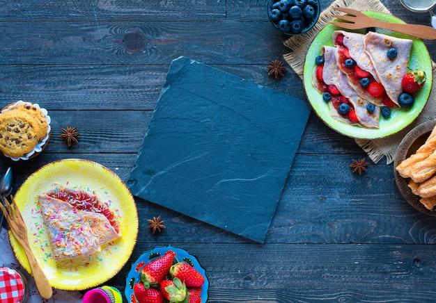 Świeże domowe naleśniki podawane na talerzu z truskawkami i jagodami, na ciemnej drewnianej powierzchni,
