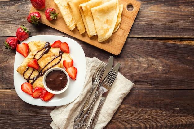 Świeże domowe naleśniki z truskawkami i sosem czekoladowym na rustykalne drewniane tła. widok z góry.