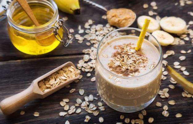 Świeże, domowe, odżywcze smoothie z bananowymi płatkami owsianymi i masłem orzechowym na drewnianym tle