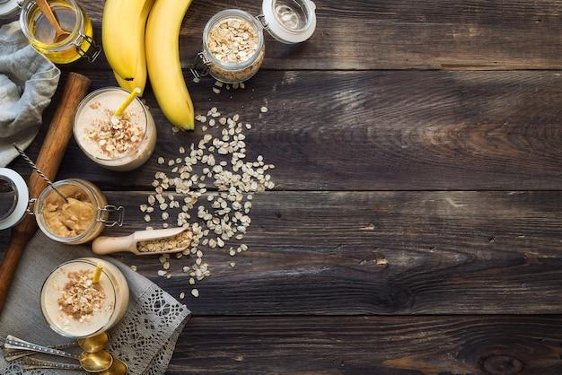 Świeże domowe, odżywcze smoothie z płatkami owsianymi bananowymi i masłem orzechowym na drewnianym tle