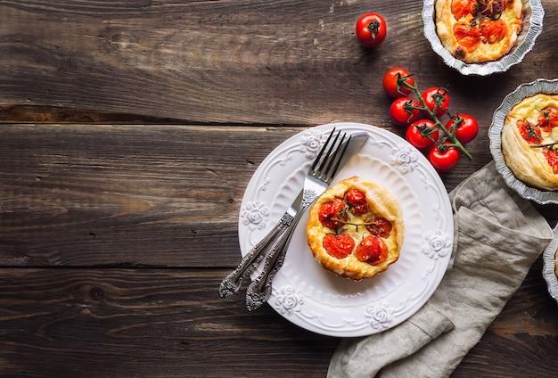 Świeże domowe tarty z pomidorkami cherry i kozim serem na rustykalne drewniane tła. widok z góry.