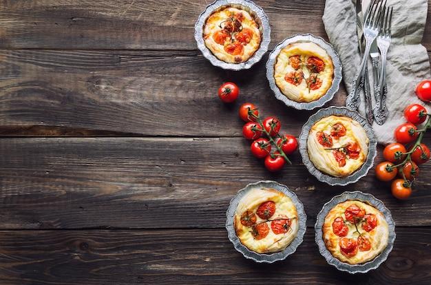 Świeże domowe tarty z pomidorkami koktajlowymi i kozim serem na rustykalne drewniane tła. widok z góry.