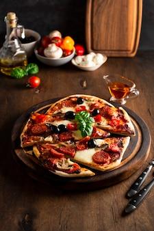 Świeże domowe włoskie pizze z mozzarellą, kiełbaskami pepperoni, oliwkami i bazylią na drewnianym stole pionowe zdjęcie. zdjęcie wysokiej jakości