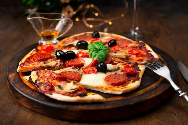 Świeże domowe włoskie pizze z mozzarellą, kiełbaskami pepperoni, oliwkami i bazylią na drewnianym stole z bliska. zdjęcie wysokiej jakości