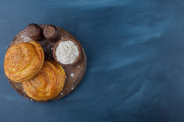 Świeże domowe wypieki i miska mąki na kawałku drewna.