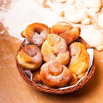 Świeże donaty z cukrem pudrem i przygotowanym ciastem