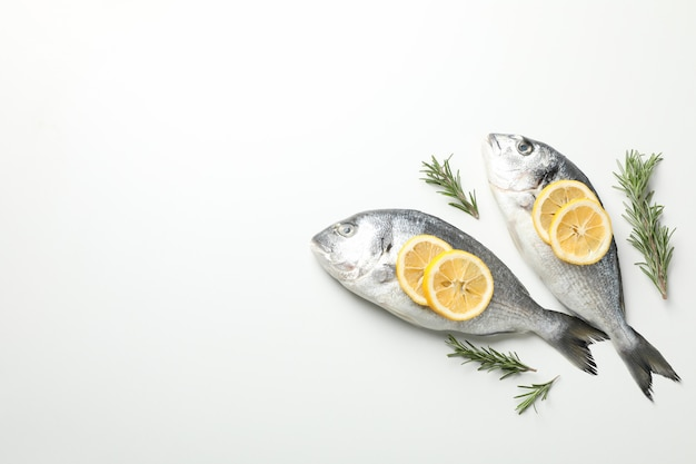 Świeże dorado ryba, cytryna i rozmaryny na białym tle, odgórny widok