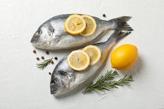 Świeże dorado ryba, pieprz, cytryna i rozmaryn na białym tle, odgórny widok