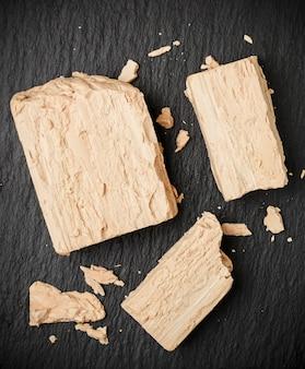 Świeże drożdże na szarym stole zbliżenie, składnik do pieczenia chleba i produktów piekarniczych