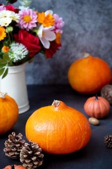 Świeże dynie. jesień kreatywny flatlay, ciemne tło ze świecami, jesienne kwiaty, szyszki i dynie. widok z góry.
