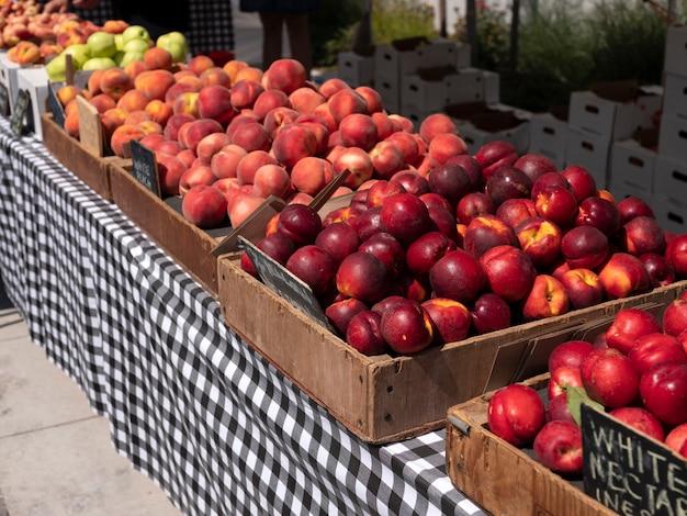 Świeże ekologiczne brzoskwinie w drewnianej skrzyni gotowe do sprzedaży na rynku rolniczym