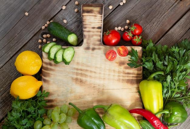 Świeże ekologiczne warzywa do gotowania wokół drewnianej deski do krojenia na rustykalnym stole z góry