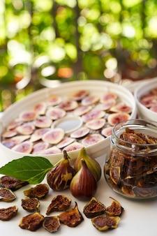 Świeże figi leżą na stole obok suszonych fig w szklanym słoju na balkonie