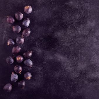 Świeże figi na ciemnym drewnianym stole, odgórny widok z kopii przestrzenią