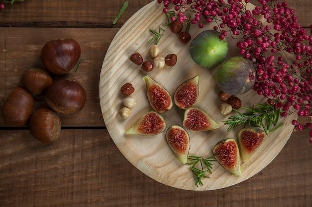Świeże figi na drewnianym talerzu z orzechami laskowymi, czerwoną papryką i rozmarynem