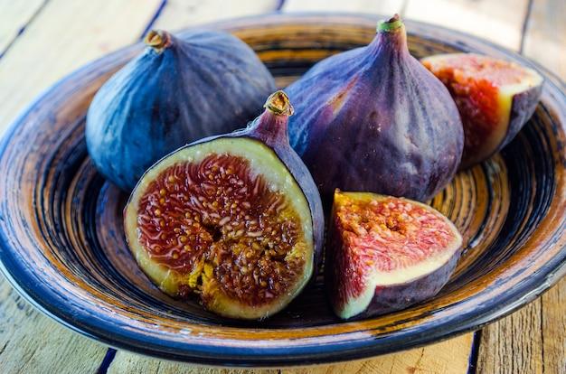 Świeże figi w misce na drewnianym stole