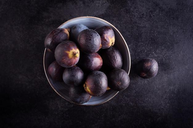 Świeże figi w pucharze na ciemnym drewnianym stole, odgórny widok z kopii przestrzenią