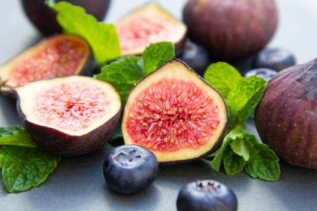 Świeże figi z miętą i jagodami. beautifulf jagoda, owocowy tło.