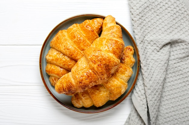 Świeże francuskie rogaliki na talerzu, serwetka na białym tle drewnianych