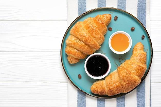 Świeże francuskie rogaliki z dżemem jagodowym, miodem i filiżanką kawy
