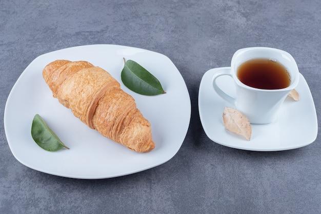 Świeże francuskie rogaliki ze złotą skórką z filiżanką herbaty.