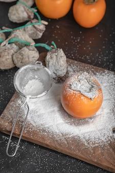 Świeże fuyu i suszone owoce persimmon na czarnej powierzchni