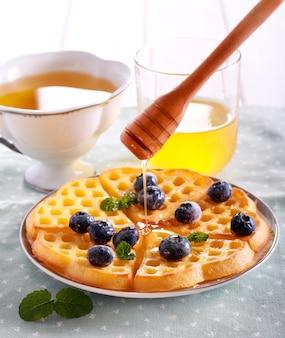 Świeże gofry, jagoda i miód na talerzu
