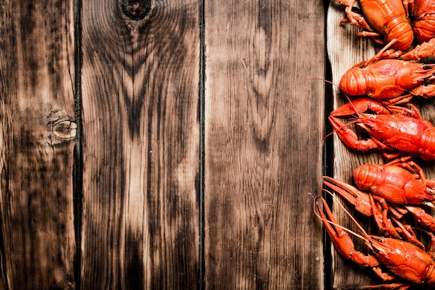 Świeże gotowane raki na starej desce do krojenia na drewnianym tle